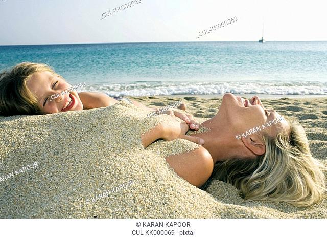 Woman buried in sand at the beach with young girl leaning on her and laughing