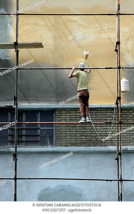 Worker standing on scaffolding and painting the wall of a building, Tehran, Iran, Asia