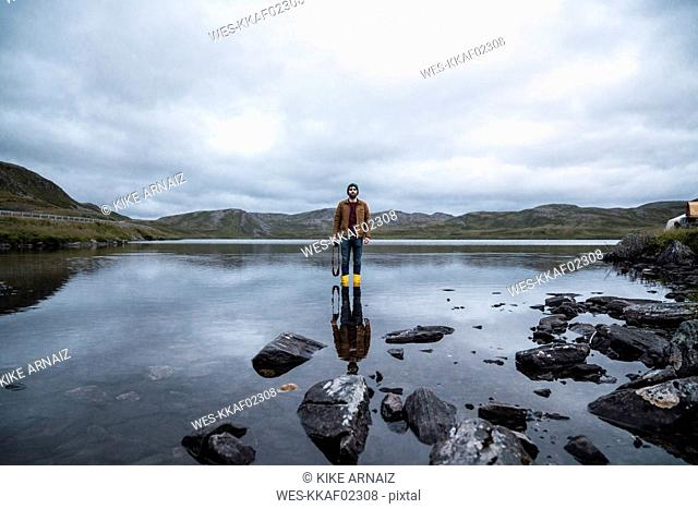 Young man standing ankle deep in water, holding camera