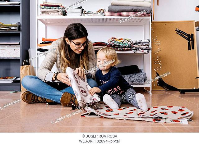 Mother and little daughter sitting on the floor at home checking fabrics