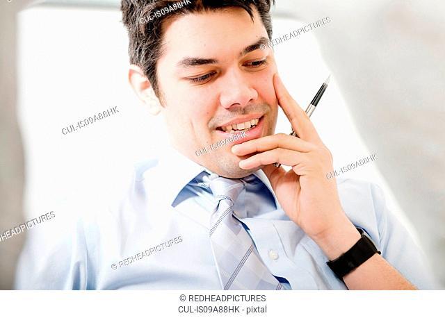 Portrait of man holding pen