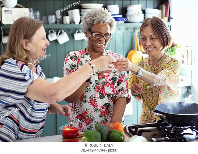 Active senior women friends cooking, toasting cocktails in kitchen