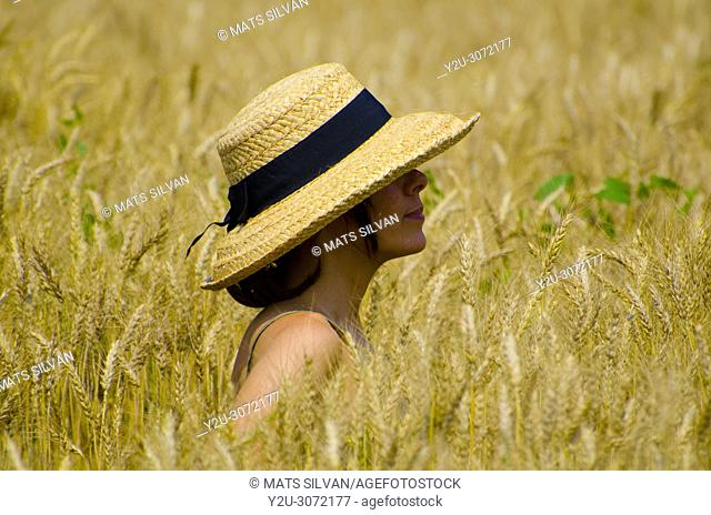 Woman with a Straw Hat Standing in a Wheat Field in Locarno, Switzerland