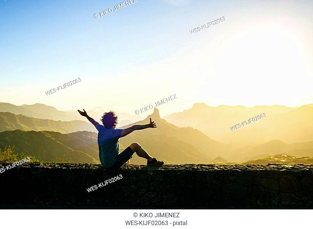 Spain, Canary Islands, Gran Canaria, back view of happy man watching mountain landscape at sunset