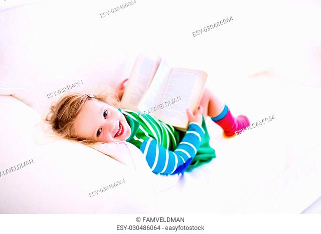Happy laughing little girl reading a book relaxing on a white couch at home