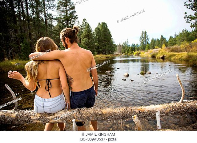 Rear view of young couple sitting on fallen tree in river, Lake Tahoe, Nevada, USA