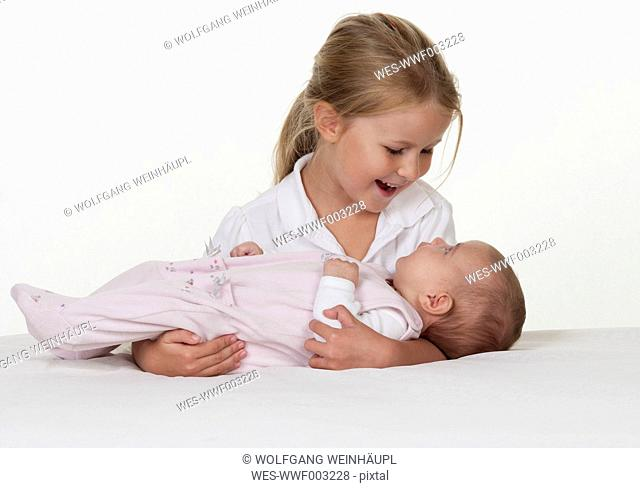 Smiling little girl holding newborn sister