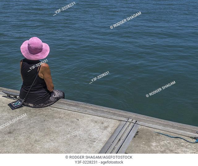 Woman sits calmly on a pier watching the sea. Port Douglas, Australia