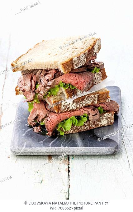 Roast beef sandwiches with lettuce on marble cutting board on blue background