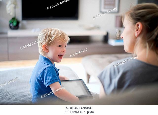 Mother and son sitting together, son holding digital tablet, laughing