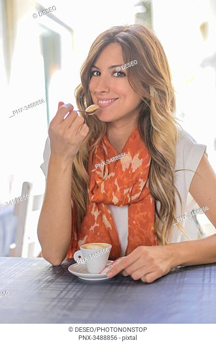 Woman enjoying a coffee in a Cafe looking at camera