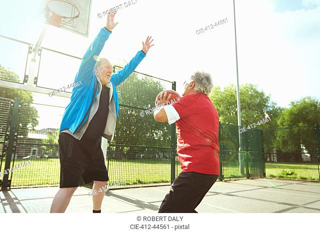 Active senior men playing basketball in sunny park