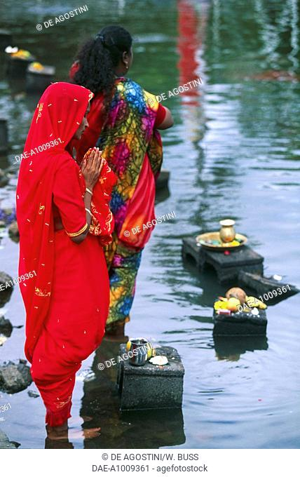 Women praying and bearing offerings of fruit and flowers to the god Shiva at Grand Bassin lake, held sacred by Hindus, Mauritius