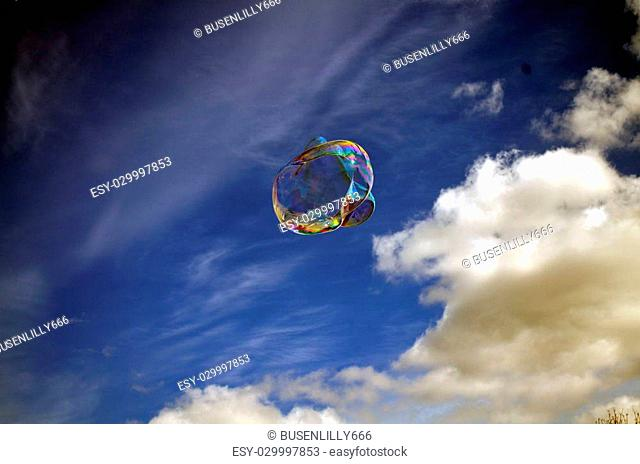 Soap rainbow bubble on blue sky background