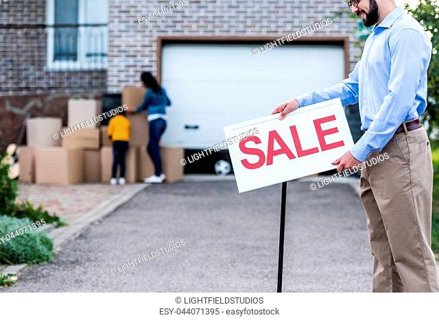 handsome young realtor with sale signboard in front of house with people moving out