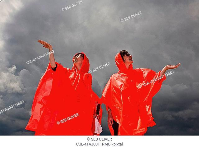 Women in ponchos feeling for rain