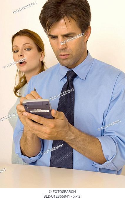 Portrait of a man using his PDA while a woman peeks over his shoulder