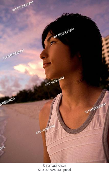 Young man smiling on beach in the evening, Saipan, USA