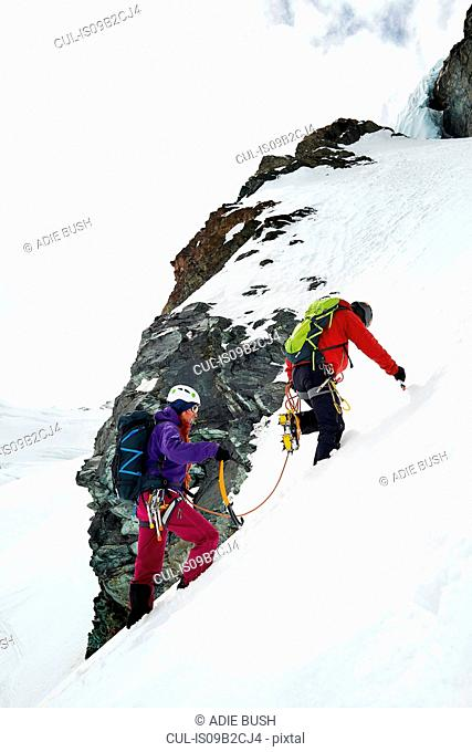 Mountaineers ascending snow-covered mountain, Saas Fee, Switzerland