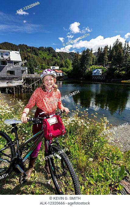 Young girl with her bicycle next to the Seldovia Slough on a sunny day, Southcentral Alaska, USA
