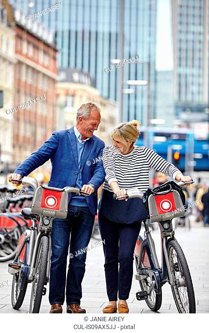 Mature dating couple laughing whilst pushing hire bicycles, London, UK
