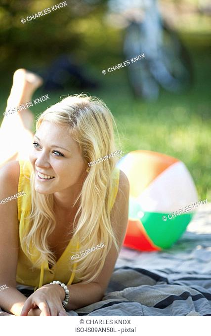 Portrait of young woman lying on picnic blanket in park
