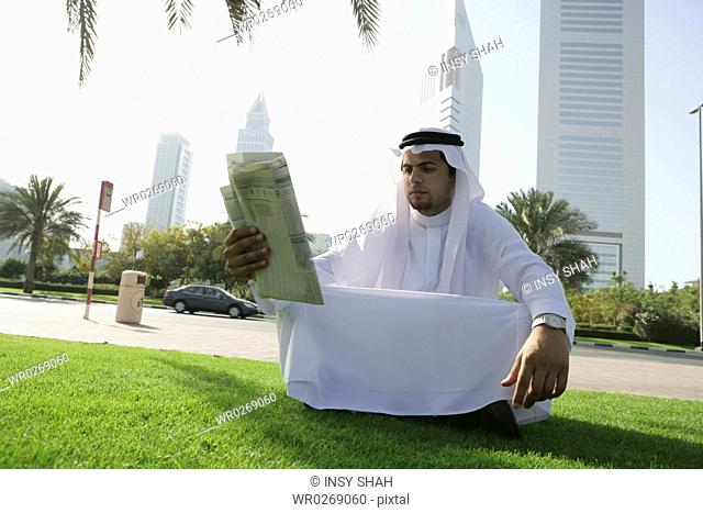Arab Men read the newspaper under the Palm Tree
