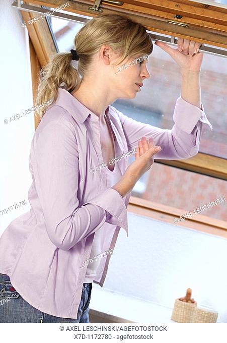 woman with headache standing near open window for fresh air