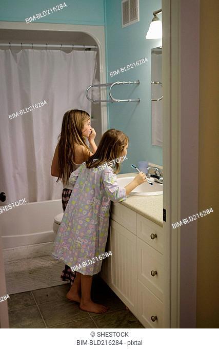 Caucasian sisters brushing teeth in bathroom