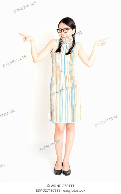 Portrait of young Asian woman in traditional qipao dress finger pointing at something, full length standing on plain background