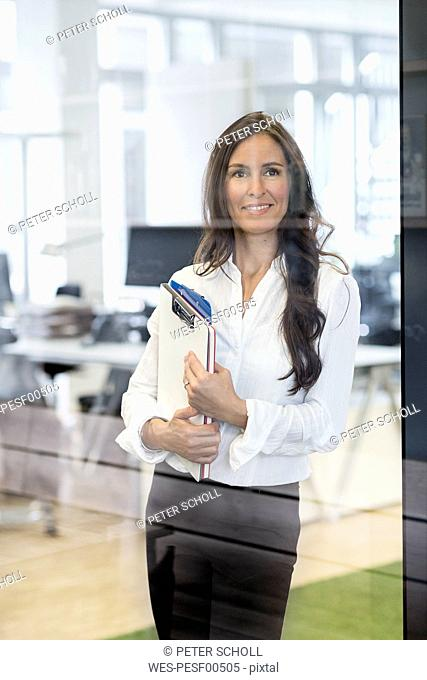 Portrait of confident businesswoman in office holding clipboard