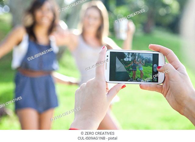 Three young female friends taking photographs with smartphone