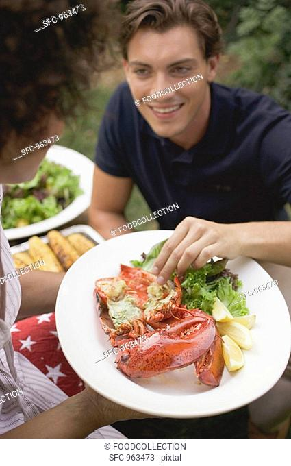Man taking a piece of lobster from a plate