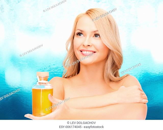 health and beauty concept - happy woman with oil bottle
