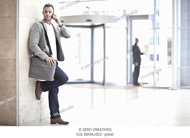 Young businessman chatting on smartphone in conference centre atrium