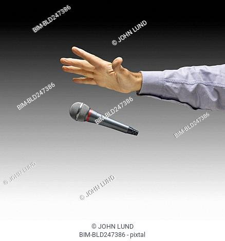 Hand of Caucasian businessman dropping microphone