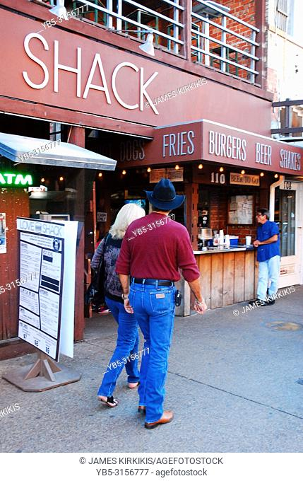 A couple strolls by the Love Shack, a popular eatery at the Fort Worth Stockyards