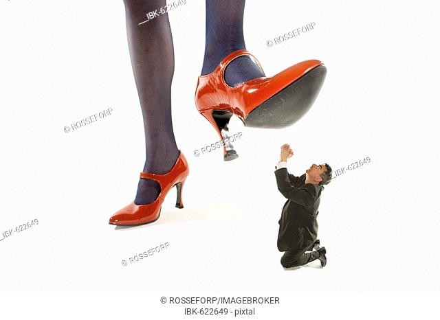 Woman in red high heels stepping on a shrunken man
