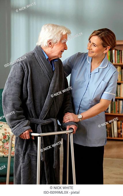 Carer assisting senior man using walking frame