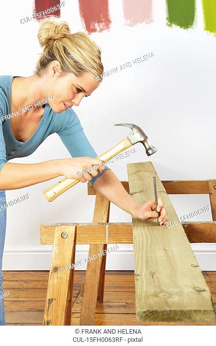 Woman hitting nail