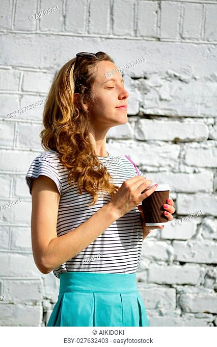 Happy young woman with a disposable coffee cup on the background old wall enjoying the morning sunshine