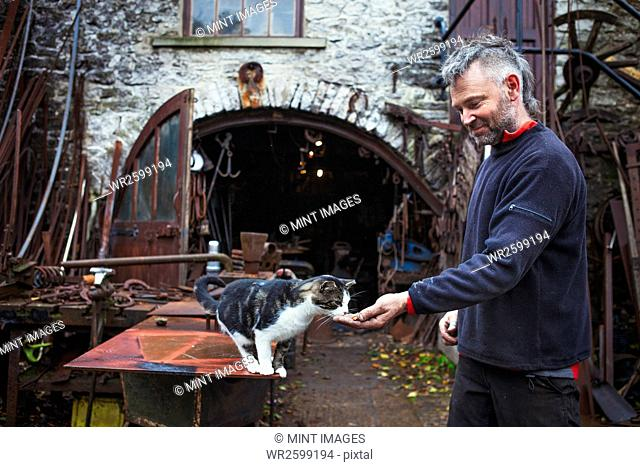 Blacksmith standing outside his workshop, feeding a cat