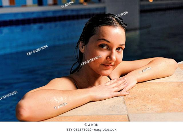 Young attractive woman relaxing in the water. pool