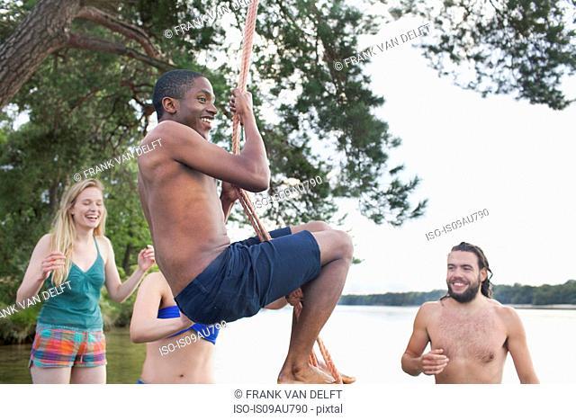 Young man rope swinging above lake