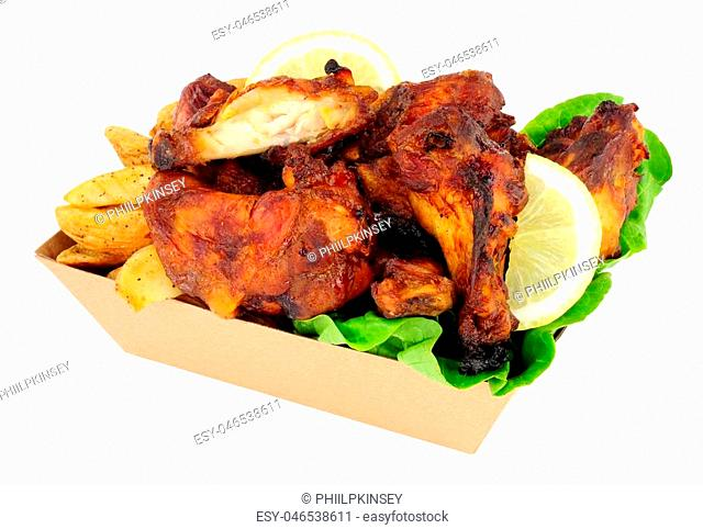Chicken wings and potato wedges in a cardboard take away tray isolated on a white background