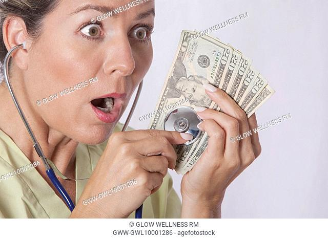 Doctor checking currency notes with a stethoscope