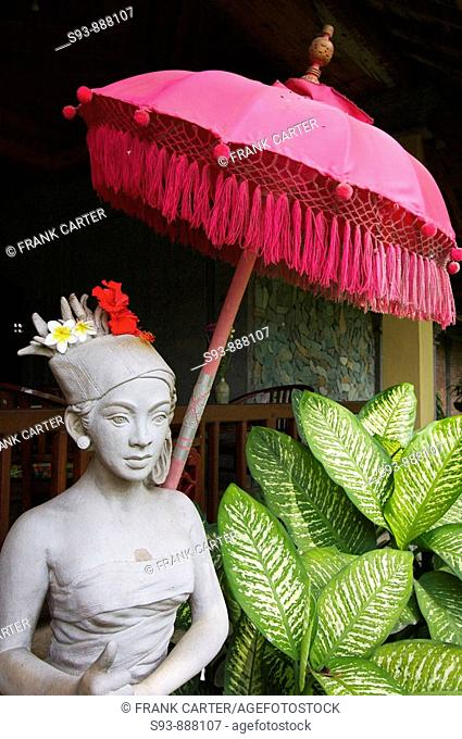 A statue of a Balinese woman decorated with flower blossoms under a red traditional Balinese umbrella in Ubud, Bali