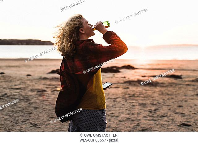 Teenage girl relaxing at the beach, having a drink