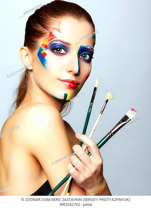Young woman painter with paint brush in hand and acrylic paint on face