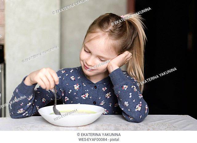 Portrait of smiling little girl eating oat meal